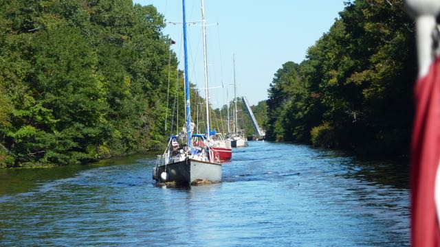 Long line of boats passing through bridge